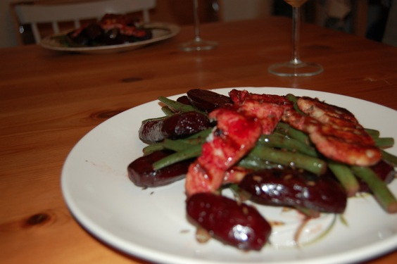 Plate of beetroot, green beans and grilled cheese on a table